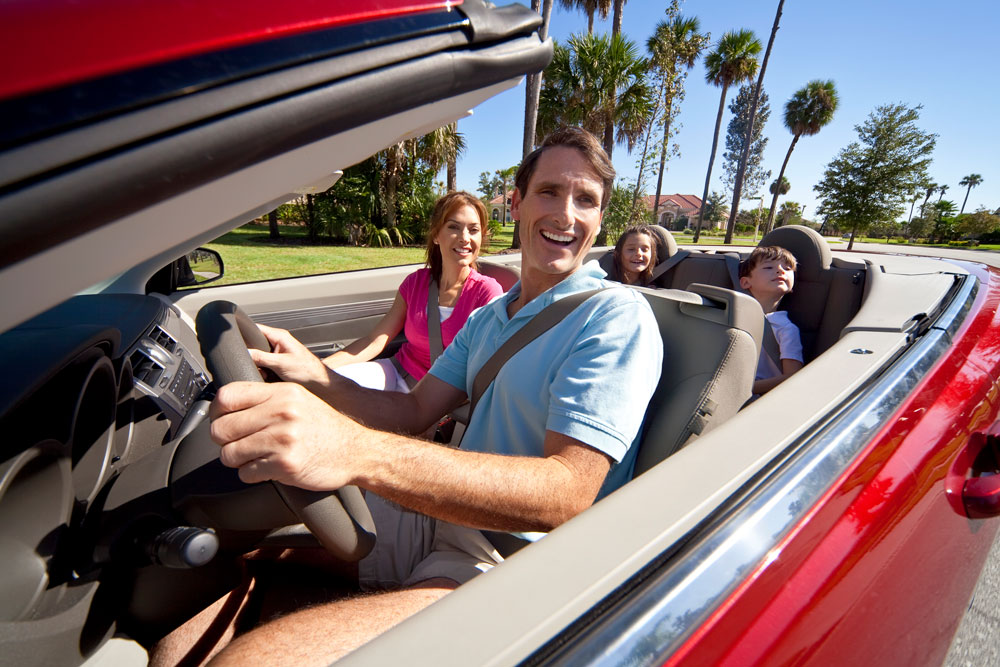 Smiling family driving convertible car in St. Petersburg, Florida